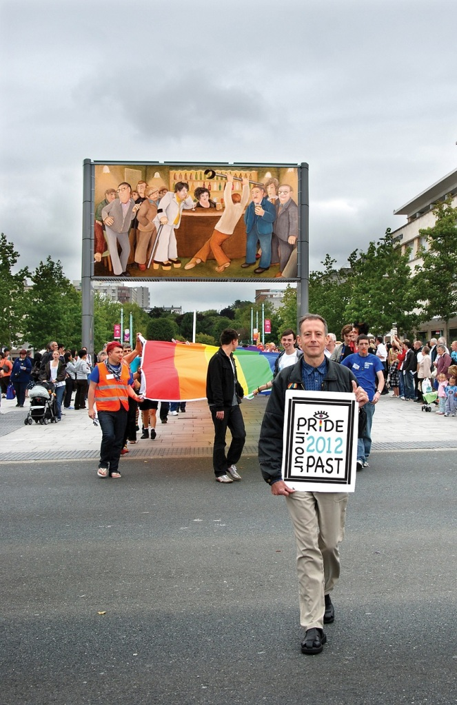 A man holding a Plymouth Pride poster on Royal Parade